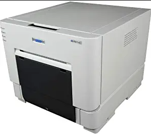 """The DNP DS-RX1HS is the ultimate all-in-one photo printer for businesses, events, and professionals looking to improve their efficiency. The advanced printing technology allows users to print 4""""x6"""" photos in just over 12 seconds, or up to 290 4""""x6"""" photos per hour.  This high-speed printer is so quick in fact that it is ideal for anyone in the event or photo business. Prints 2""""x6"""" photos with QuickSnap technology for quick set up and tear down.  The DNP Event Photo Printer DS-RX1HS 6 is a powerful and high-performance printer that will allow you to print, process and share your event photos in real time.  The printer features a large 6 inch touchscreen that makes it easy to navigate through the menu.   The high resolution of the photos that are being printed is of 100ppi with a 1200 x 1200 dpi resolution. And if you have more than one DNP Event Photo Printer DS-RX1HS 6, you can connect them together to print larger photos in a same time. You can connect the printers with MTP connections or USB cables."""
